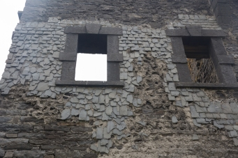 The building was faced with overlapping slate tiles. They have only survived on the protected face.